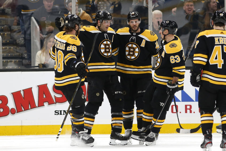 Boston Bruins' Patrice Bergeron, second from left, celebrates his goal against the Washington Capitals with David Pastrnak (88), Brad Marchand and David Krejci during the first period of an NHL hockey game Monday, Dec. 23, 2019, in Boston. (AP Photo/Winslow Townson)