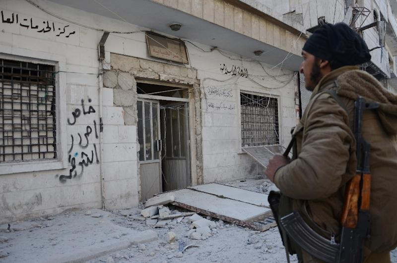 A Syrian rebel stands on February 24, 2017 outside a building previously belonging to Islamic State (IS) group fighters (AFP Photo/Nazeer al-Khatib)