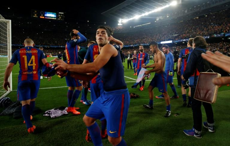 Barcelona forward Luis Suarez prepares to throw his shirt to the fans as he celebrates their 6-1 victory in the Champions League round of 16 second leg against Paris Saint-Germain FC at the Camp Nou stadium in Barcelona on March 8, 2017