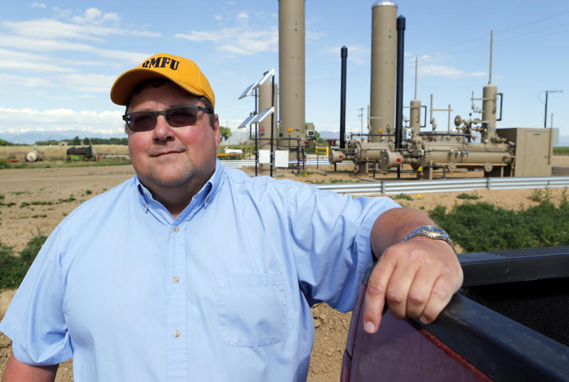 In this Friday, June 7, 2013 photo farmer Kent Peppler stands for his photo in front of two gas wells on his land near Greeley, Colo. Both wells were fracked according to Peppler. Peppler says he is fallowing some of his corn fields this year because he can't afford to irrigate the land, in part because deep-pocketed energy companies have driven up the price of water. (AP Photo/Ed Andrieski)