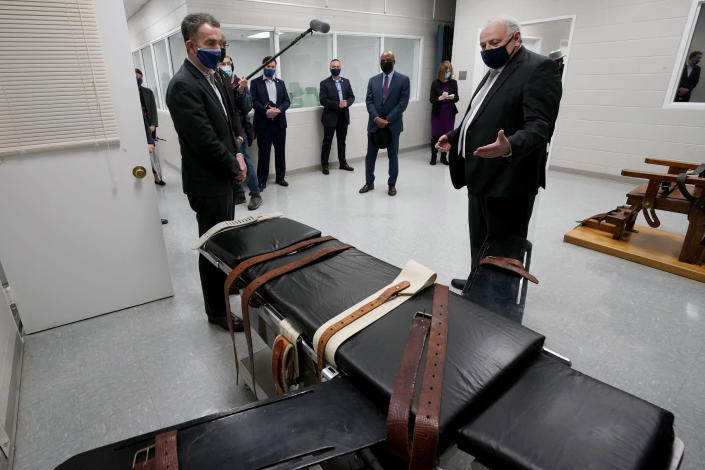 IMage: Virginia Gov. Ralph Northam looks at a gurney at Greensville Correctional Center with Operations Director George Hinkle on March 24, 2021. (Steve Helber / AP)