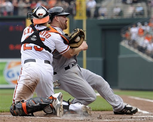 Boston Red Sox's Kevin Youkilis, right, is tagged out by Baltimore Orioles catcher Luis Exposito (25) on a double by Red Sox's Will Middlebrooks during the third inning of a baseball game, Wednesday, May 23, 2012, in Baltimore. (AP Photo/Nick Wass)