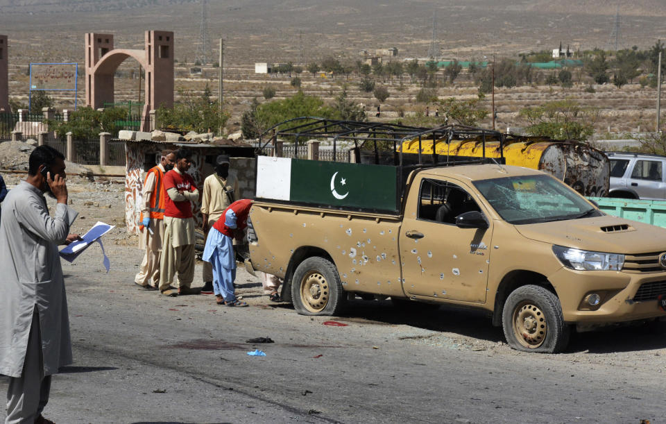 Security officials examine the site of suicide bombing in a checkpoint on the outskirts of Quetta, Pakistan, Sunday, Sept. 5, 2021. A suicide bomber detonated his explosives Sunday near the security checkpoint in restive southwestern Pakistan, killing few paramilitary troops and wounding more than a dozen, police said. (AP Photo/Arshad Butt)