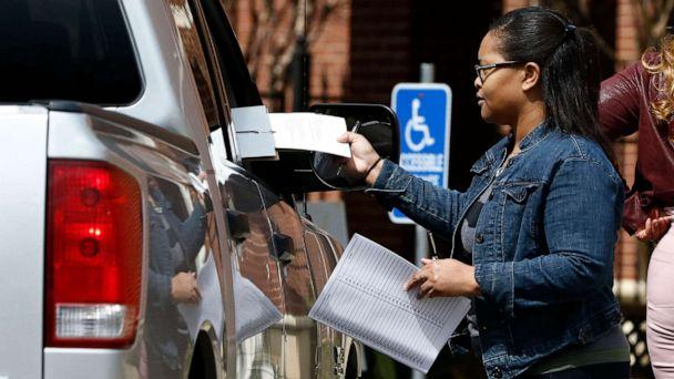 PHOTO: Amour Fowler, a Jackson, Miss., precinct poll manager delivers a ballot to a curbside voter in Jackson, Miss., March 10, 2020. (Rogelio V. Solis/AP)