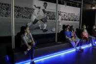 People watch a film about Brazilian soccer legend Pele at an exhibition marking his 80th birthday at the Soccer Museum in Sao Paulo