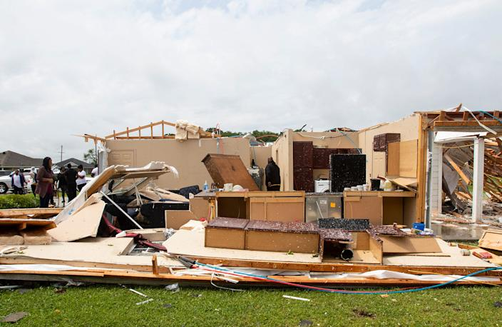 Neighbors inspect a house for occupants in Monroe, La. after an Easter tornado ripped through the town just before noon on April 12, 2020. (Nicolas Galindo/The News-Star via AP) ORG XMIT: LAMON206