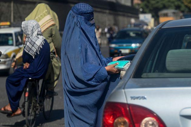 An Afghan burqa clad woman sells face masks to the commuters at a traffic intersection in Kabul on September 5, 2021. (Photo by Aamir QURESHI / AFP) (Photo by AAMIR QURESHI/AFP via Getty Images) (Photo: AAMIR QURESHI via Getty Images)