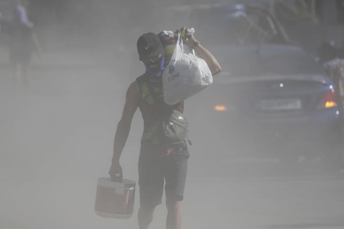 A man walks the his belongings through clouds of ash kicked up on a road as authorities enforced total evacuation of residents living near Taal volcano in Agoncillo town, Batangas province, southern Philippines on Thursday Jan. 16, 2020. Taal volcano belched smaller plumes of ash Thursday but shuddered continuously with earthquakes and cracked roads in nearby towns, which were blockaded by police due to fears of a bigger eruption. (AP Photo/Aaron Favila)