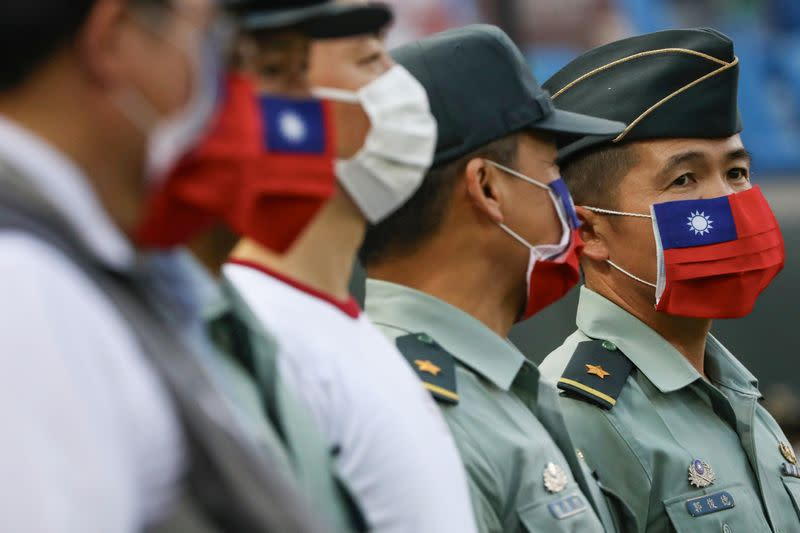 Army representative are seen at the opening of a baseball game with face masks decorated as a Taiwan flag to protect themselves from the coronavirus disease (COVID-19) at a professional baseball league game at Taoyuan International baseball stadium