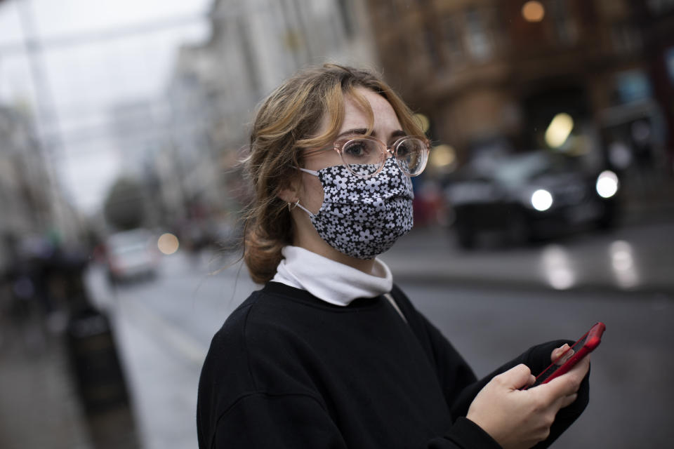 "LONDON, ENGLAND - OCTOBER 13: A woman wears a face mask while passing through Oxford Circus on October 13, 2020 in London, England. London Mayor Sadiq Khan said today that the city would move into Tier 2 of the government's new Covid-19 risk classification once it hits 100 new daily cases per 100,000 people, which could happen this week. The second or ""high"" tier of the three-tier system triggers a ban on household mixing, although pubs would remain open. (Photo by Dan Kitwood/Getty Images)"
