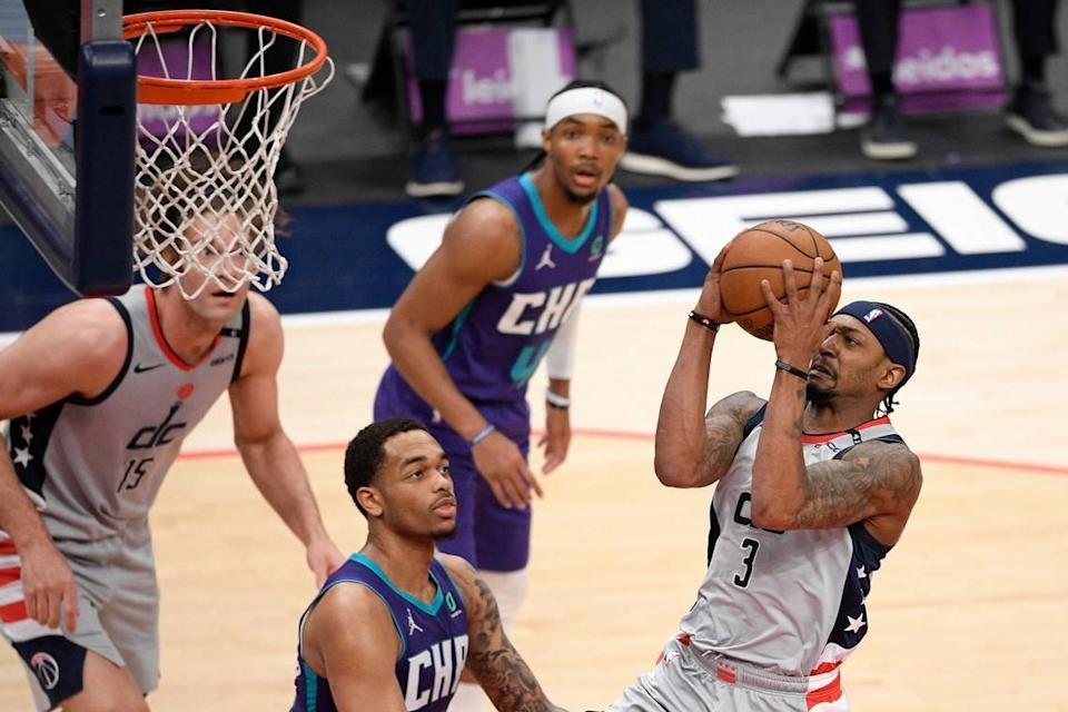 Washington Wizards guard Bradley Beal (3) goes to the basket against Charlotte's P.J. Washington, center, during the first half of Washington's 115-110 win Sunday.