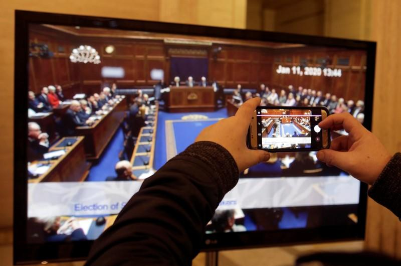 Man films a television screen on his phone in the great hall, Stormont as politicians in Northern Ireland returned to the Stormont Assembly after backing a deal to restore devolution in Belfast