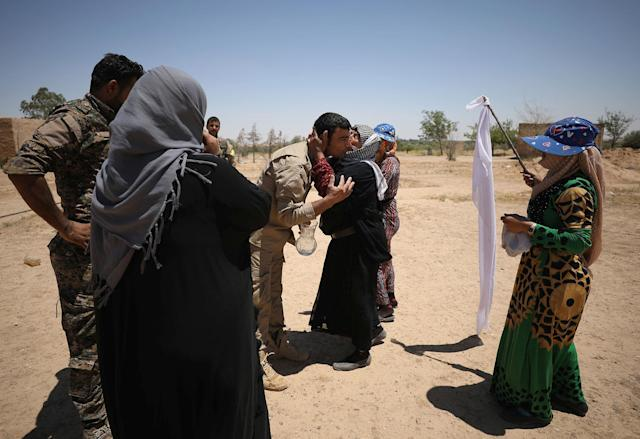 <p>A woman, who fled with others from an Islamic State-controlled area, greets Syrian Democratic Forces (SDF) fighters near Raqqa city, Syria June 7, 2017. (Photo: Rodi Said/Reuters) </p>