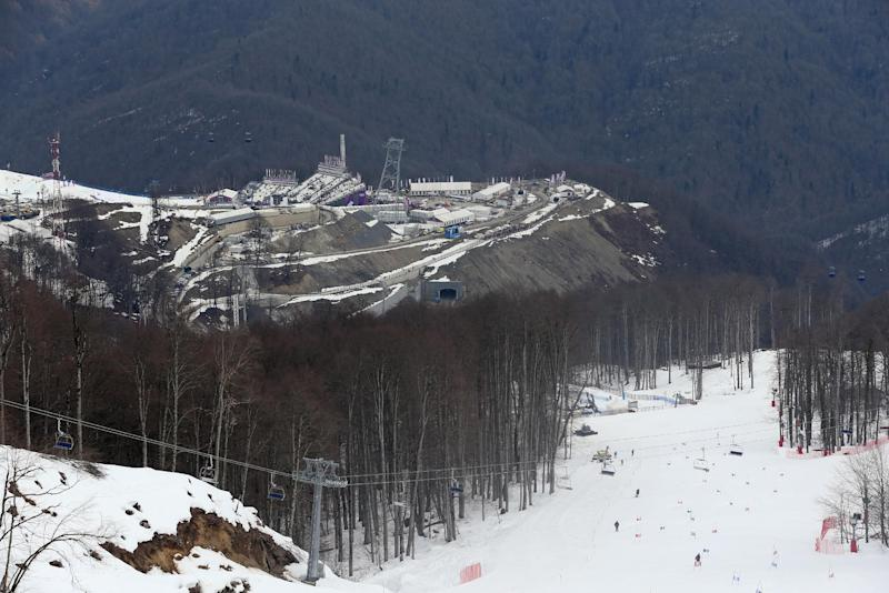 A view from near the alpine course showing the difference between the snow covered piste and the snowless lower slopes at the Sochi 2014 Winter Olympics, Tuesday, Feb. 11, 2014, in Krasnaya Polyana, Russia. Warm temperatures in the mountains made the snow too soft and caused the cancellation of women's downhill training on Tuesday. (AP Photo/Luca Bruno)
