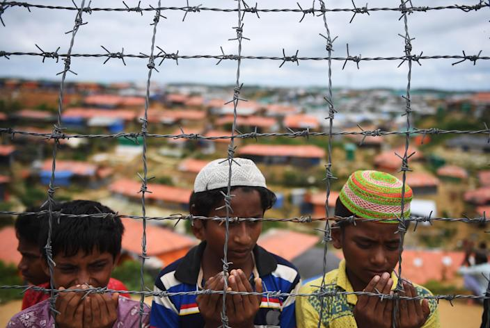 Rohingya refugees pray at a ceremony to remember the first anniversary of a military crackdown that prompted a massive exodus of people from Myanmar to Bangladesh, at the Kutupalong refugee camp in Ukhia on Aug. 25, 2018.