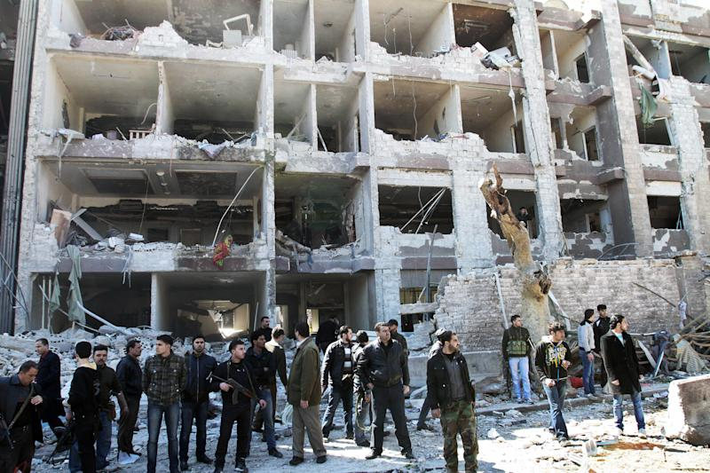 FILE - In this Saturday, March 17, 2012 file photo, Syrian security officers gather in front the damaged building of the aviation intelligence department, which was attacked by one of two explosions in Damascus, Syria. A new al-Qaida-style group claimed Wednesday, March 21, 2012 that it carried out the double suicide bombing that killed dozens. Syria's uprising is taking on increasingly religious tones, and Islamic groups - from al-Qaida-style militants to the politically moderate Muslim Brotherhood - are jumping on board. (AP Photo/Bassem Tellawi, File)