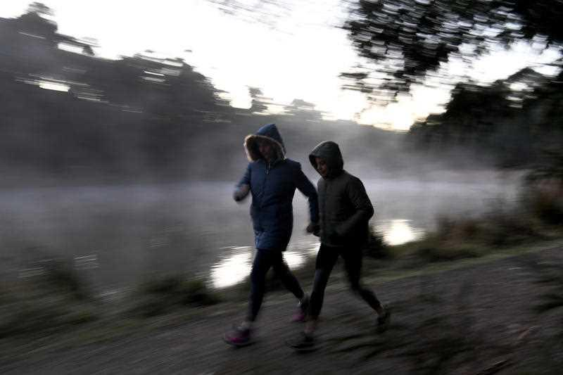 Two early walkers brave the cold weather at Birdsland reserve in Belgrave South, east of Melbourne.
