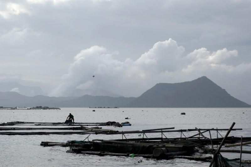 A man catches fish as the Taal Volcano erupts in the background in Talisay