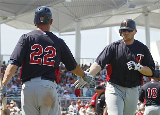 Minnesota Twins' Chris Parmelee, right, is congratulated by Danny Valencia (22) after his home run against the Boston Red Sox during the sixth inning of a spring training baseball game in Fort Myers, Fla., Sunday, April 1, 2012. (AP Photo/Charles Krupa)