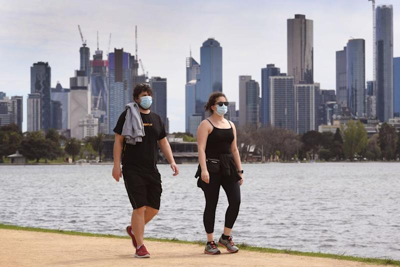 Pictured are two people in Melbourne wearing face masks.