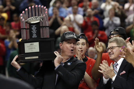 FILE - North Carolina State head coach Wes Moore holds the championship trophy following an NCAA college basketball championship game against Florida State at the Atlantic Coast Conference women's tournament in Greensboro, N.C., in this Sunday, March 8, 2020, file photo. At right looking on is ACC commissioner John Swofford. (AP Photo/Gerry Broome, File)