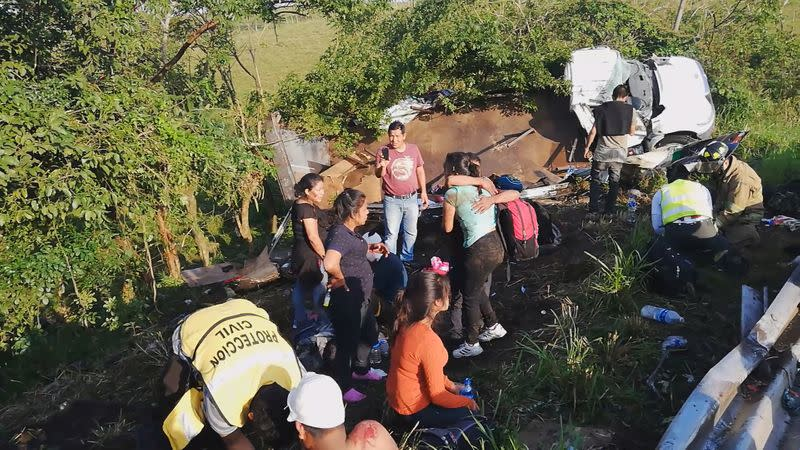 Migrants are treated by first responders following a crash on a highway in San Andres Tuxtla