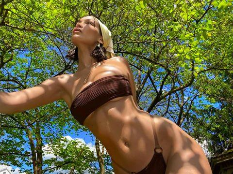 "<p>For a throwback post, Bella Hadid shared a carousel of images of herself posing beneath a tree in a bandana and bikini. The soon-to-be new Aunt captioned the at-home shoot: 'May 29.2020 Day 92 of soul searching in these mf trees 🍃.'</p><p><a href=""https://www.revolve.com/juillet-emma-bikini-bottom-in-chesnut/dp/JUIL-WX34/"" target=""_blank"">Bella's bikini bottoms are available to buy</a> at Revolve now, and while the top is sold out, there's a <a href=""https://www.revolve.com/juillet-kirke-bikini-top/dp/JUIL-WX23/"" target=""_blank"">similar version available here</a>. </p><p><a href=""https://www.instagram.com/p/CCemKUgAk83/"">See the original post on Instagram</a></p>"