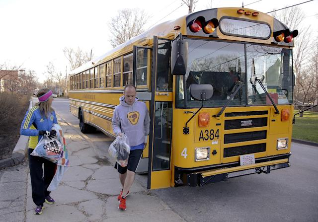 Runners in the 118th Boston Marathon disembark a bus as they arrive near the start line Monday, April 21, 2014 in Hopkinton, Mass. (AP Photo/Stephan Savoia)