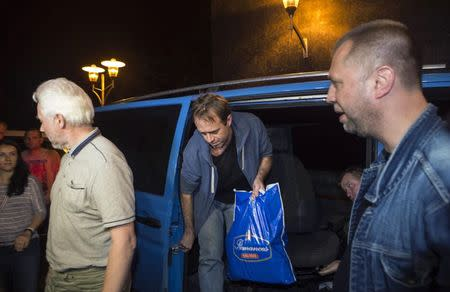 "Unidentified members of OSCE Special Monitoring Mission in Ukraine get out of a vehicle next to Alexander Borodai (R), Prime Minister of the self proclaimed ""Donetsk People's Republic"", on arrival at the city of Donetsk after being released from captivity, June 27, 2014. REUTERS/Shamil Zhumatov"