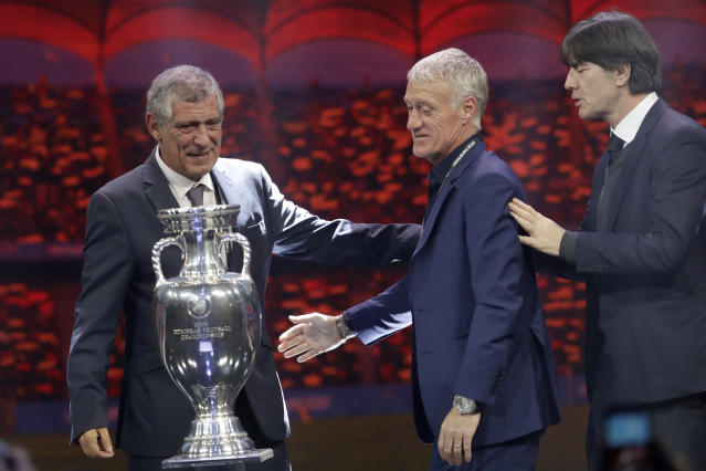 The coaches of Portugal Fernando Santos, Germany Joachim Loew and France Didier Deschamps, from left to right, who will play in group F, pose with the trophy after the draw for the UEFA Euro 2020 soccer tournament finals in Bucharest, Romania, Saturday, Nov. 30, 2019. (AP Photo/Petr David Josek)