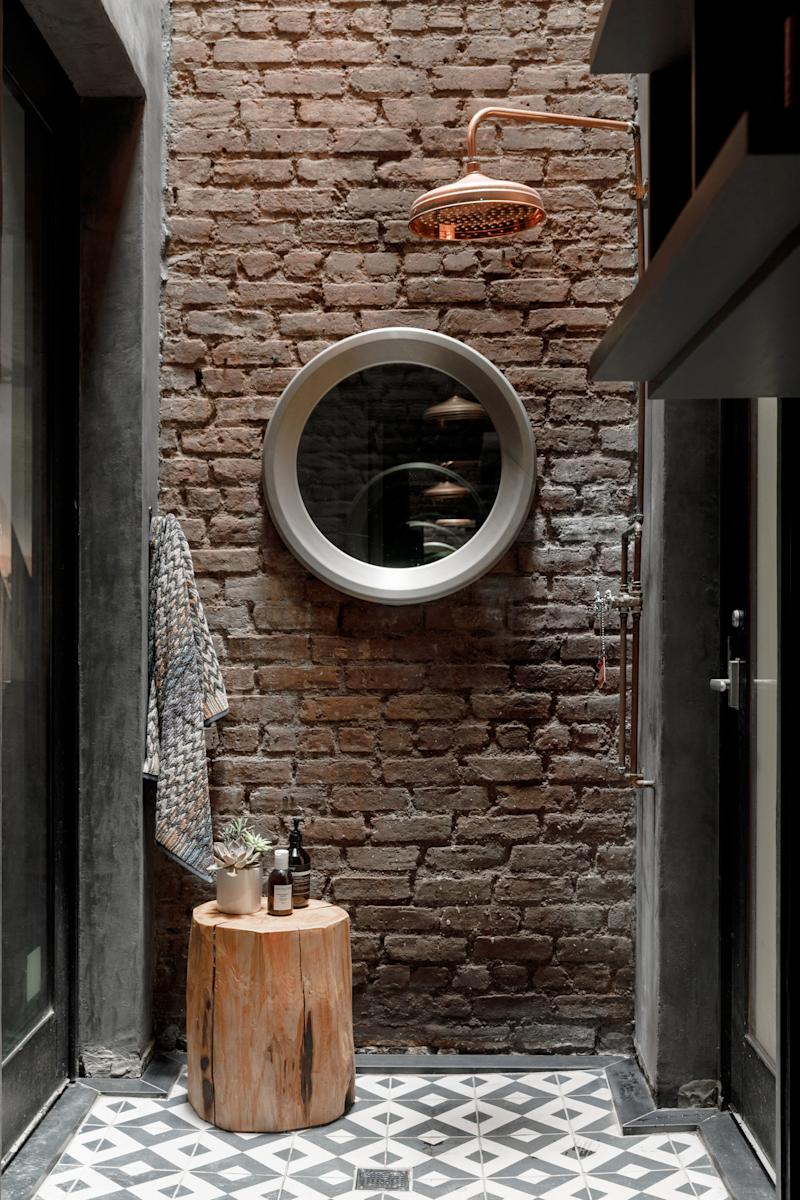 """While the notion of bathing outdoors in New York City might seem unappealing, Tierney contends it's """"heaven."""" But then, her outdoor shower, which was built (on her suggestion) where an air shaft had been, and outfitted with Moroccan tiles and a copper Newport Brass showerhead, is a strikingly unique setup. """"Even when it's snowing outside, it gets steamy in there,"""" she says."""
