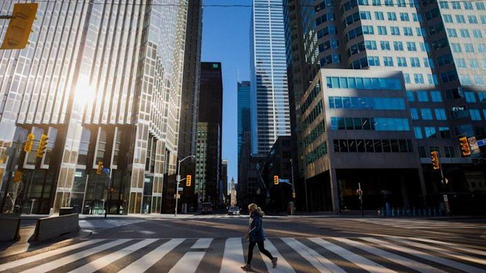 A woman crosses the street during a morning commute in the financial district to deal with a coronavirus shutdown in Toronto, Canada on April 1, 2020.