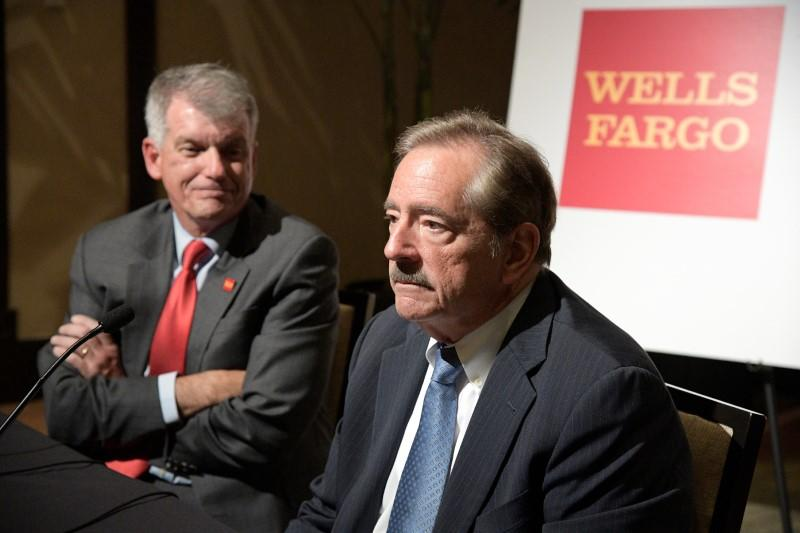 Wells Fargo CEO Tim Sloan (L) listens as Chairman Stephen Sanger answers a question from reporters after the annual shareholder meeting in Jacksonville