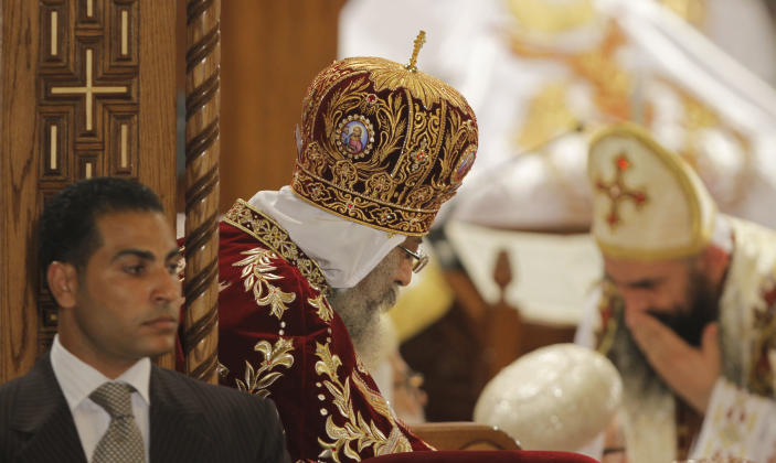An Egyptian policeman guards Pope Tawadros II, the 118th pope of the Coptic Church of Egypt, center, as he leads the Easter Mass at St. Mark's Cathedral in Cairo, Egypt, late Saturday May 4, 2013. Egypt's Coptic Christians, who make up about 10 percent of the country's 85 million people, have long complained of discrimination by the state. They are the largest Christian community in the Middle East. (AP Photo/ Amr Nabil)