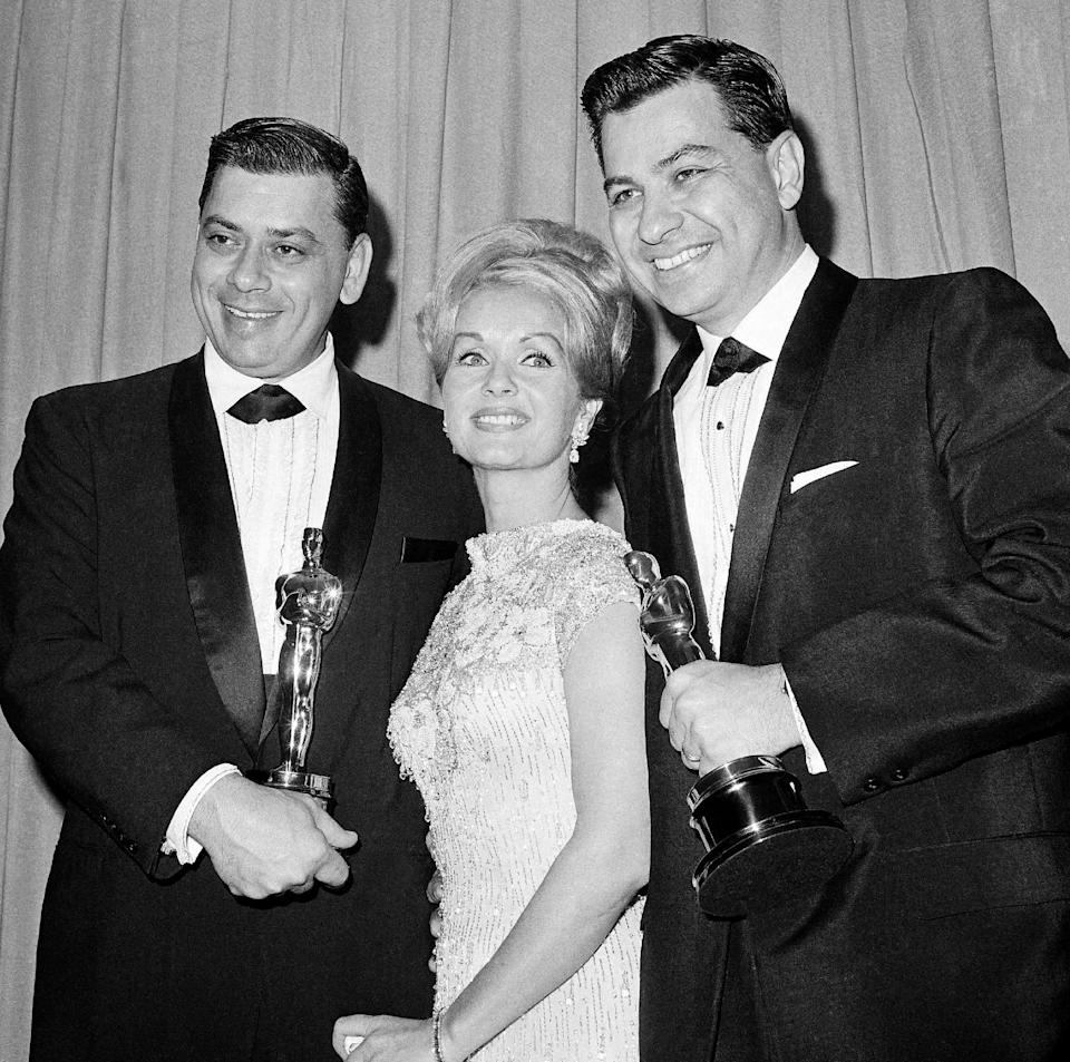 """FILE - In this April, 5,1965 file photo actress Debbie Reynolds poses with Academy awards winners for best music Richard M. Sherman, right and Robert Sherman, left, who received the award for Mary Poppins in Santa Monica Calif. Songwriter Sherman, who wrote the tongue-twisting """"Supercalifragilisticexpialidocious"""" and other enduring songs for Disney classics, has died. He was 86. (AP Photo,File)"""