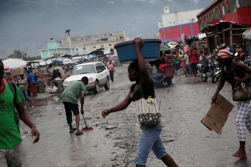 A man sweeps a street after Isaias swept through Port-au-Prince (REUTERS)