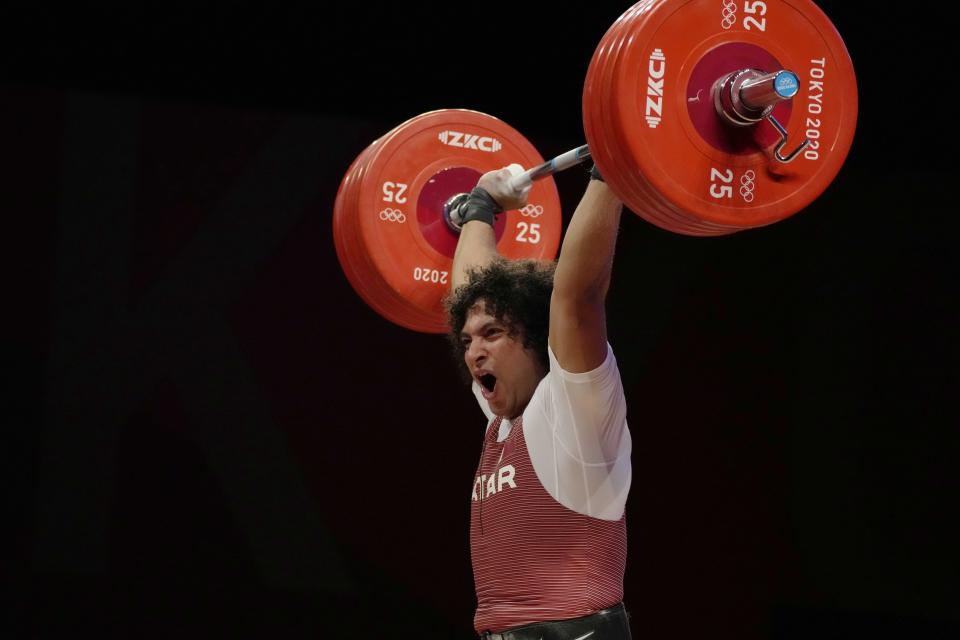Fares Ibrahim Elbach of Qatar ccompetes in the men's 81kg weightlifting event, at the 2020 Summer Olympics, Saturday, July 31, 2021, in Tokyo, Japan. (AP Photo/Luca Bruno)