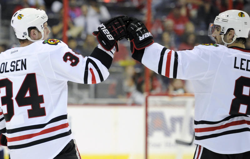 Chicago Blackhawks defenseman Dylan Olsen (34) celebrates his goal with teammate Nick Leddy (8) during the first period an NHL preseason hockey game against the Washington Capitals, Friday, Sept. 20, 2013, in Washington. (AP Photo/Nick Wass)