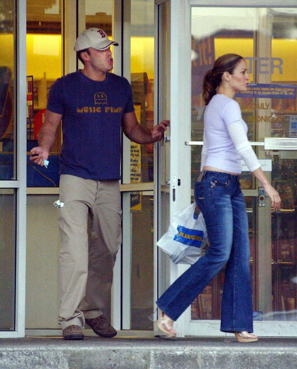 """<p>A very """"stars, they're just like us"""" moment with Ben in khakis and J.Lo in denim and heels at a Blockbuster Video in June 2003.</p>"""