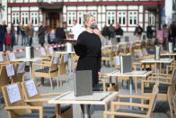 Waitress Alin Lepetit stands in the outdoor area of a café on the market square during an action to open the outdoor gastronomy, Wernigerode, Germany, Wednesday, March 3, 2021. Behind her, passers-by watch from behind a barrier tape. Numerous businesses also took part in the action nationwide. (Matthias Bein/dpa via AP)