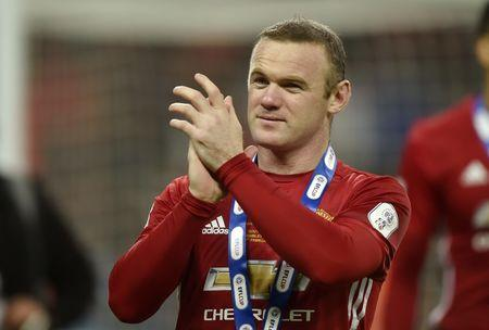 Manchester United's Wayne Rooney applauds fans as he celebrates winning the EFL Cup Final