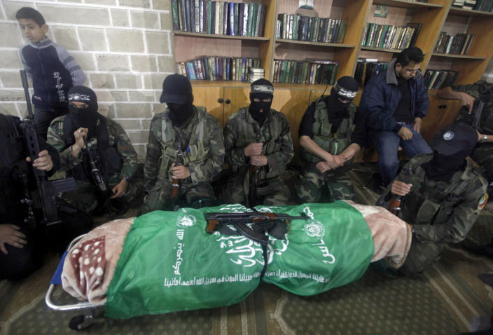 """Masked Hamas militants knell next to the flagged-draped body of Hamas member of the Palestinian Parliament Mariam Farhat, 64, who died early Sunday at the Gaza hospital in Gaza City, Sunday, March 17, 2013. Farhat, known as the """"mother of martyrs,"""" lost three of her six sons, all three Hamas militants, in fighting with Israel. (AP Photo/Hatem Moussa)"""