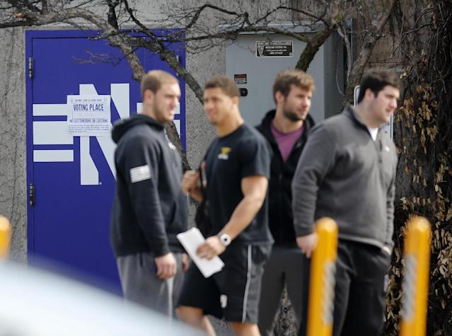 Unidentified Northwestern football players stand outside McGaw Hall and near a polling place sign where voting is taking place on the student athlete union question Friday, April 25, 2014, in Evanston, Ill. Northwestern football players cast secret ballots Friday in an on-campus hall adjacent to their home stadium on whether to form the nation's first union for college athletes. (AP Photo/Charles Rex Arbogast)