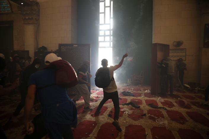 Palestinians inside the Al-Aqsa mosque clash with Israeli security forces at the Al-Aqsa Mosque compound in Jerusalem's Old City Monday, May 10, 2021.