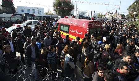 People surround an ambulance carrying the bodies of the victims of an attack by gunmen on Tunisia's national museum in Tunis March 18, 2015. REUTERS/Zoubeir Souissi