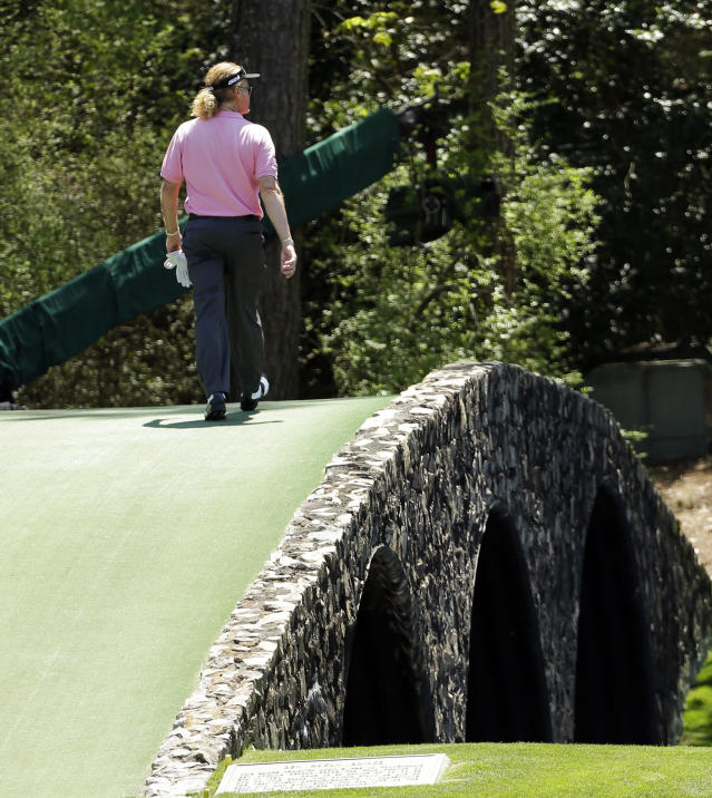 Miguel Angel Jimenez, of Spain, walks across the Hogan Bridge on the 12th fairway during the first round of the Masters golf tournament Thursday, April 10, 2014, in Augusta, Ga. (AP Photo/David J. Phillip)