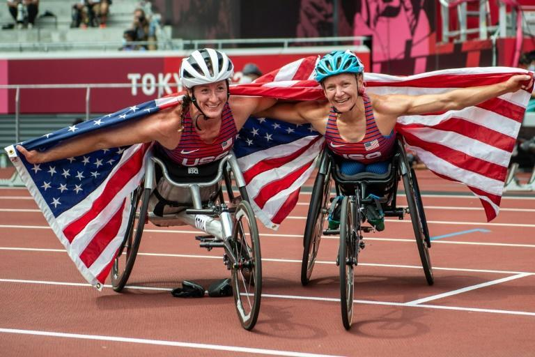 Tatyana McFadden (L) and Susannah Scaroni celebrate after winning bronze and gold, respectively, in the women's 5,000m T54 (AFP/Philip FONG)