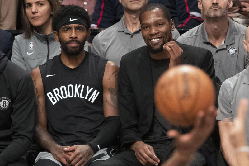 "Kyrie Irving in a shirt that says ""Brooklyn"" on the bench with Kevin Durant in a black suit and a basketball in the foreground."