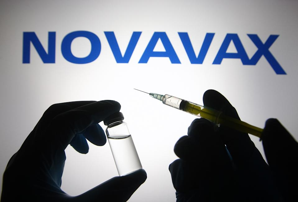 UKRAINE - 2021/04/27: In this photo illustration, silhouette of hands in medical gloves hold a medical syringe and a vial in front of Novavax logo. (Photo Illustration by Pavlo Gonchar/SOPA Images/LightRocket via Getty Images)