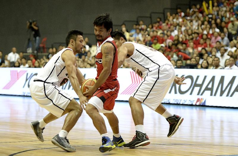 World boxing champion Manny Pacquiao (C) plays for and coaches the Kia Carnival basketball team (AFP Photo/Noel Celis)
